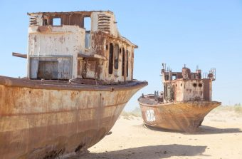 Rustic boats on a ship graveyards on a desert around Moynaq